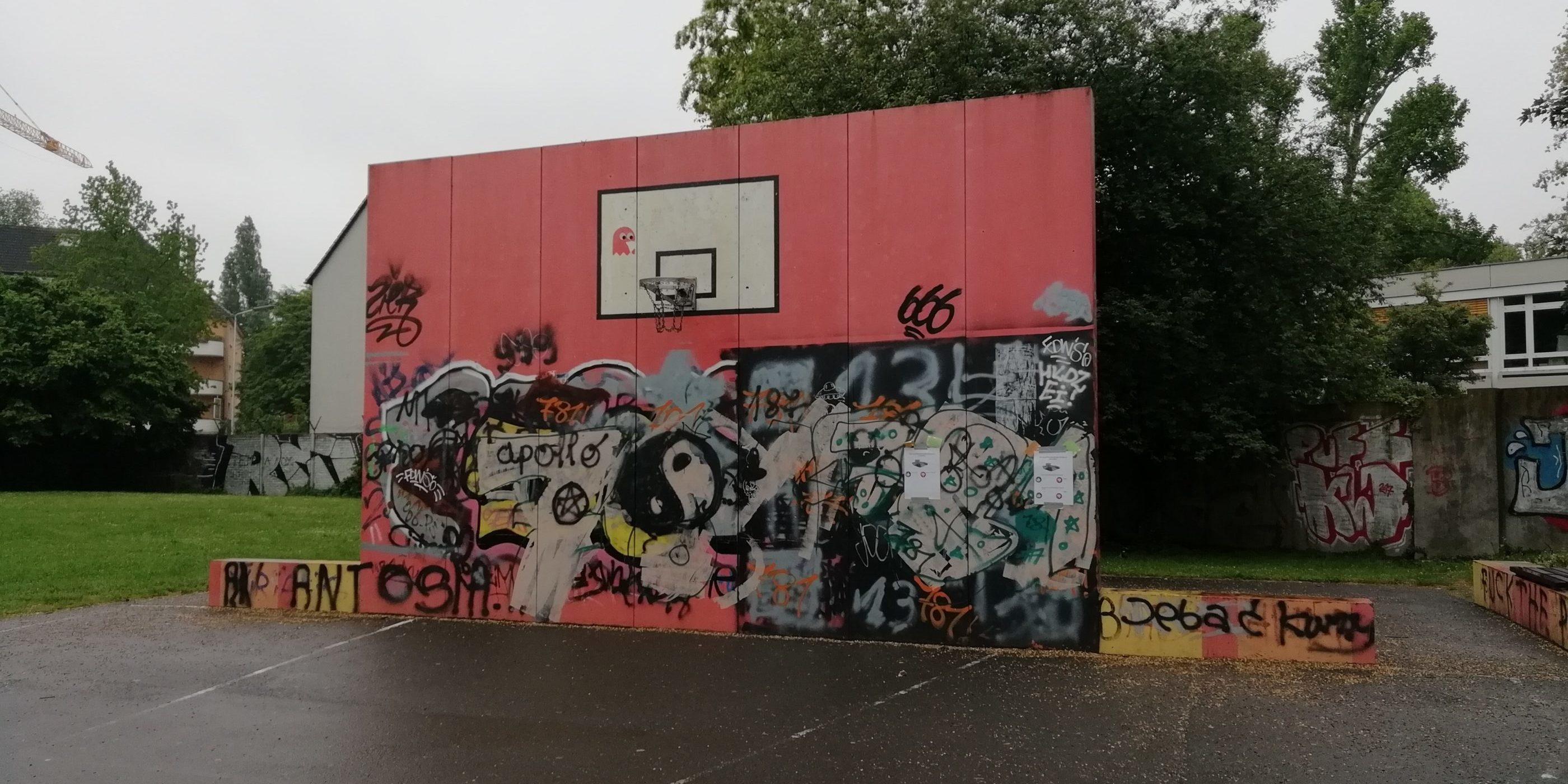 Basketballfeld mit vielen Graffitis an der Wand vom Korb