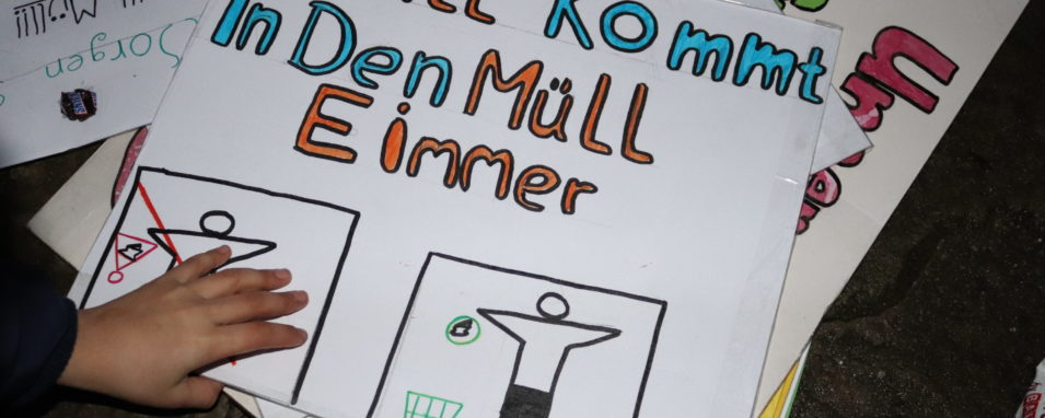 """Gebastetes Schild """"Müll kommt in den Eimer"""" mit Kinderhand"""