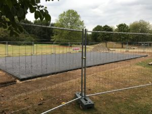 Baustelle mit neuem Sportfeld hinter Bauzaun