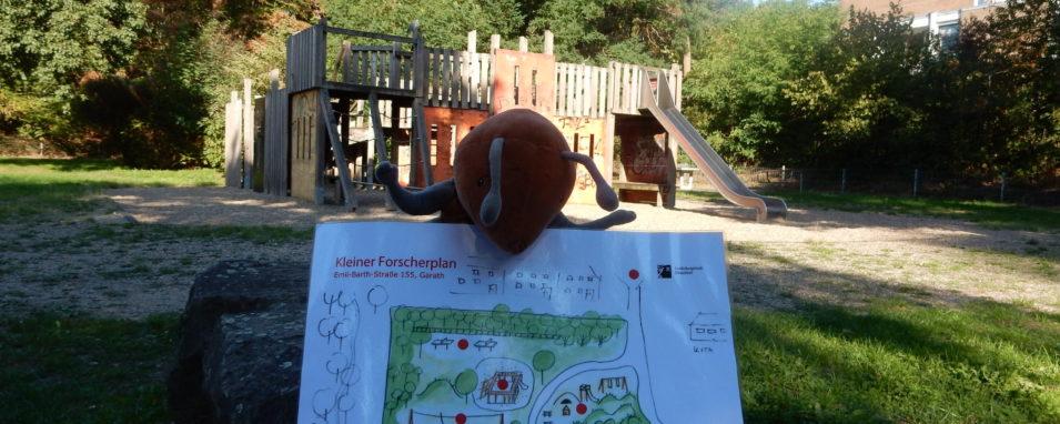 Plüschameise hält Plan vom Ameisenspielplatz vor der Kulisse des alten Spielplatzes