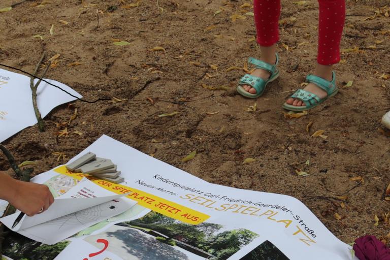 Plakat mit Vorschlägen für Neugestaltung liegt im Sand